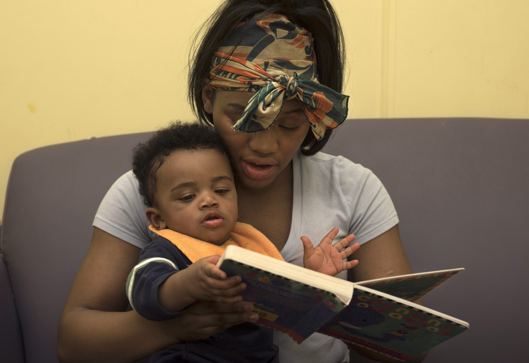Tyneisha Wilder, 18, reads to her son Tayden, age 8 months, during a supervised visit at CYF Lexington office in Point Breeze. Tayden was four days old when he was taken from Tyneisha and put into foster care. (Photo by Martha Rial/PublicSource)