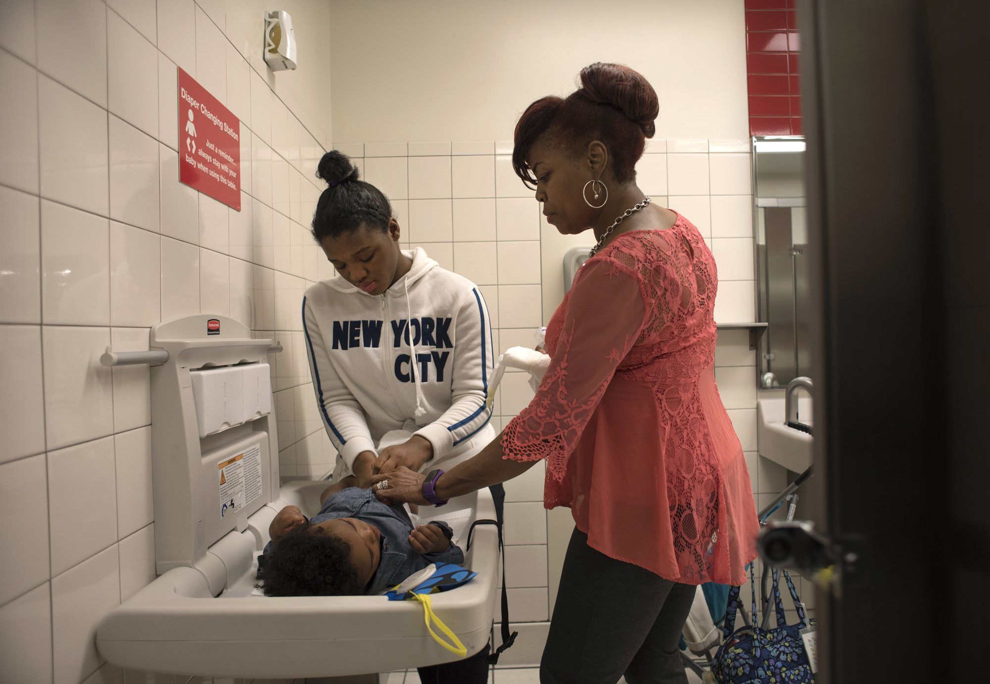 Adrienne Bradshaw, (right) helps Tyneisha Wilder, age 18, change Tayden's diaper in the restroom at Target in East Liberty during one of their twice-weekly supervised visits. (Photo by Martha Rial/PublicSource)