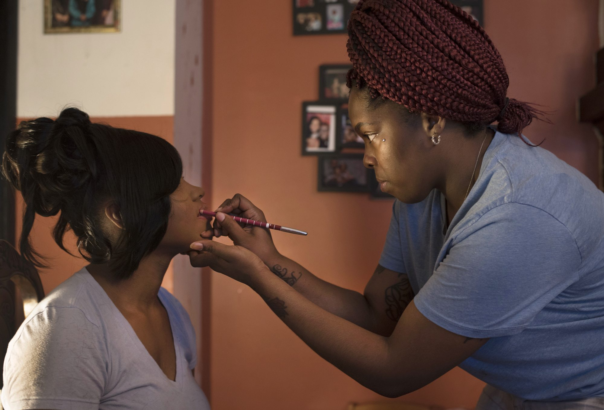 Michelle White (right) applies lip liner to Tyneisha Wilder during preparations East Allegheny High School's prom at Tyneisha's foster home in Wilkinsburg. (Photo by Martha Rial/PublicSource)