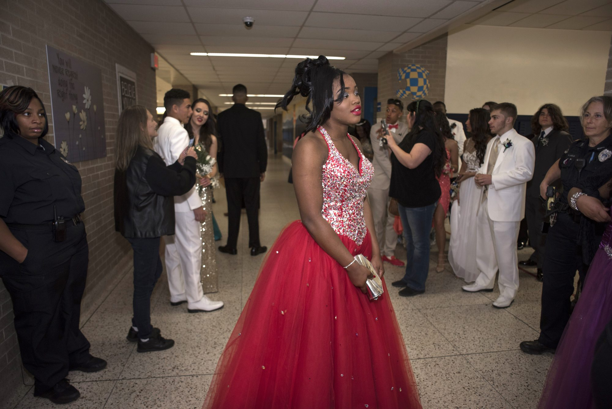 Tyneisha Wilder watches her friend and prom date pose for photographs in the lobby of East Allegheny High School in North Versailles before Prom. Wilder will graduate in June. (Photo by Martha Rial/PublicSource)